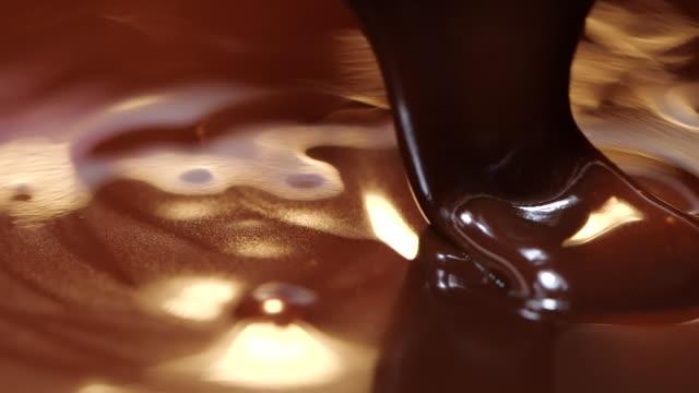 pouring dark melted chocolate in slow motion, close-up liquid dark chocolate - decorazione per dolci video stock e b–roll
