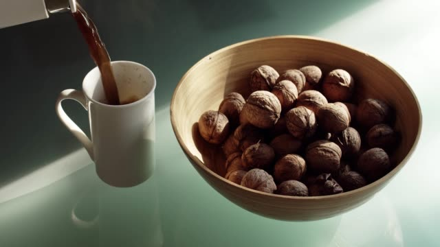 pouring drink into a cup near the dish of walnuts - noci video stock e b–roll