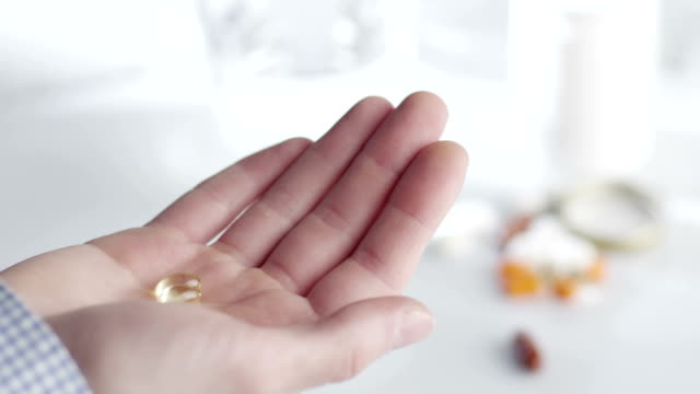 Pouring Fish Oils From Bottle into Hand video