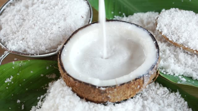 pouring fresh coconut milk and coconut fruit ingredient on bowl closeup pouring fresh coconut milk and coconut fruit ingredient on bowl coconut stock videos & royalty-free footage