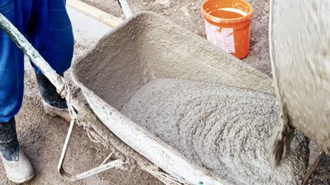 time-lapse pouring fresh concrete from the mixer into a wheelbarrow - calcestruzzo video stock e b–roll