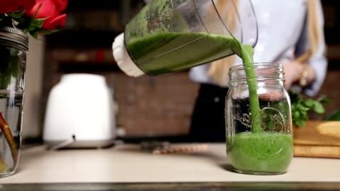versando frullato verde fresco dal frullatore in barattolo - alimentazione sana video stock e b–roll