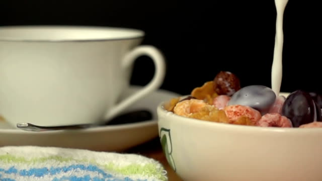 vídeos de stock e filmes b-roll de pouring fresh milk to a bowl of cereal breakfast - granola