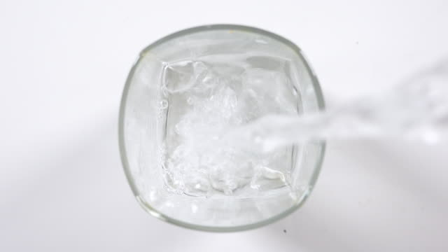 stockvideo's en b-roll-footage met gietend vers mineraalwater in glas op een lijst, hoogste mening. verse fonkelende drank met zuurstofballen op witte achtergrond - bovenkleding