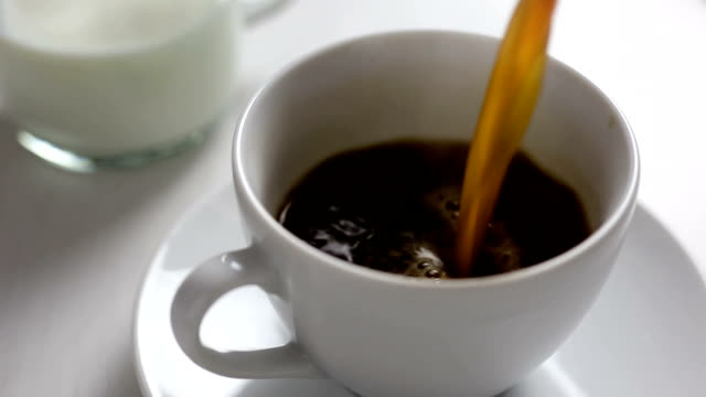 Pouring freshly brewed black coffee in a white ceramic cup.