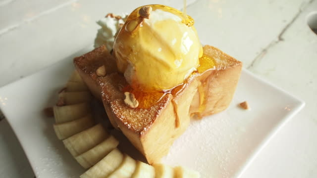pouring golden honey onto the ice cream on the toast. Slow motion