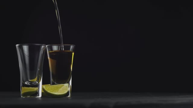 pouring golden tequila in two glasses on a black background on a rotating black board. pour of alcohol drink vodka tequila. close-up shot. . 4k video. 59.94 fps - rum superalcolico video stock e b–roll