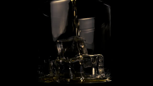Pouring Golden whiskey into a glass with ice cubes on a black background. Thin stream