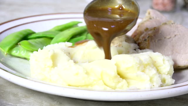 Pouring gravy over mashed potatoes