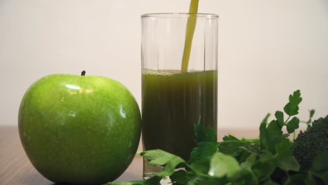 pouring green juice into glass - healthy green juice video stock e b–roll