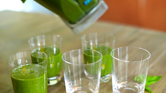 Pouring green smoothies in glasses video