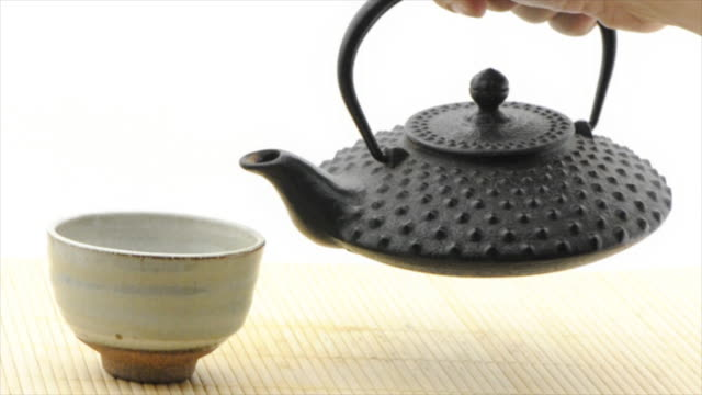 pouring green tea from tetsubin pot - white background (hd720p) - tea cup stock videos & royalty-free footage