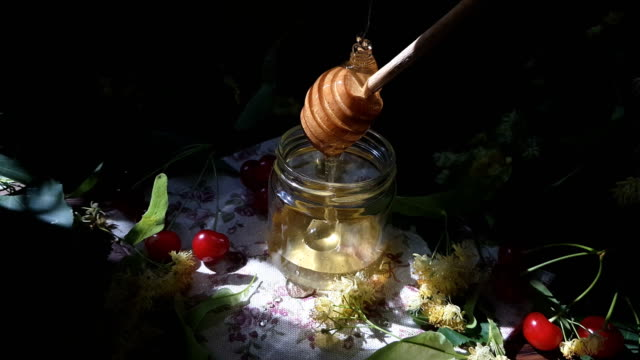 Pouring honey into glass jar, bunch of linden flowers and red cherry on wooden surface. Ray of sunlight. Dark rustic style. video
