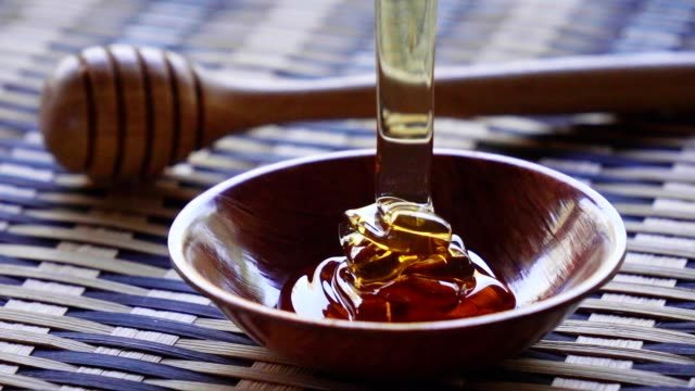 vídeos de stock e filmes b-roll de pouring honey on a wooden cup slow motion - mel