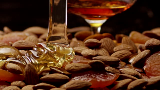 Pouring honey on almond. Shot on RED EPIC Cinema Camera. video