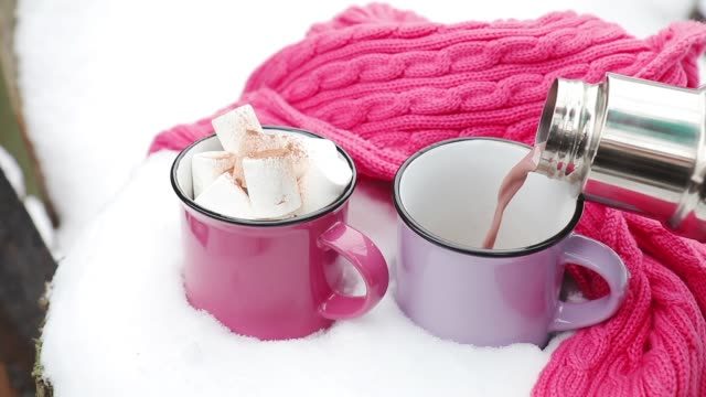 Pouring hot chocolate in the cup. Hot chocolate with marshmallow in pink and violet two cups wrapped in a cozy winter pink scarf on the snow-covered table in the garden.