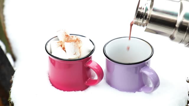 Pouring hot chocolate in the cup. Hot chocolate with marshmallow in pink and violet two cups wrapped in a cozy winter pink scarf on the snow-covered table in the garden. video