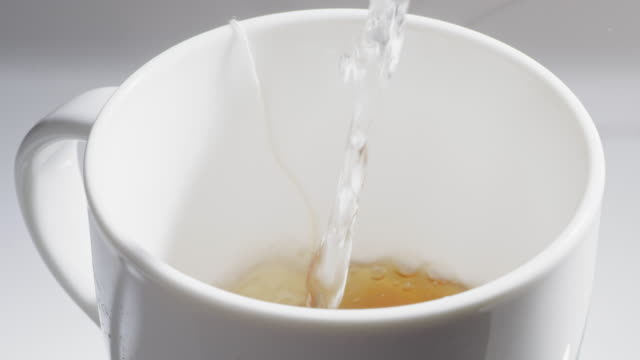 Pouring hot water into a cup of tea Pouring hot water into a cup of tea in slow motion mug stock videos & royalty-free footage