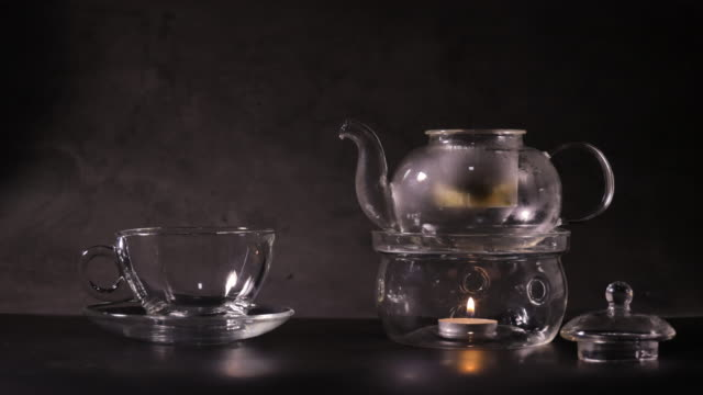Pouring hot water to make green tea into teapot on kitchen. classic teapot made from glass and boil water by candle. hot drink and tea time concept