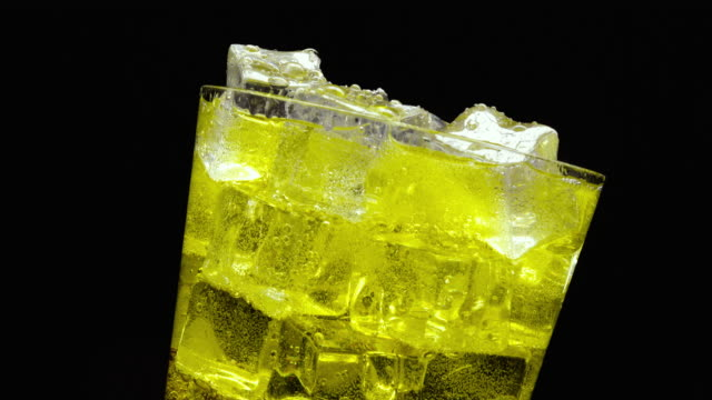 Pouring Inca Kola soda into a glass of ice on a black background