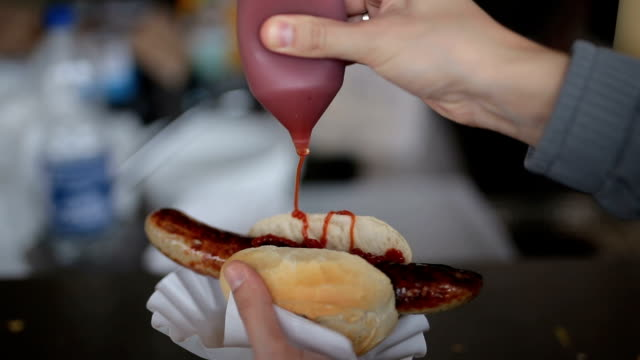 vídeos de stock, filmes e b-roll de derramando ketchup sobre o salsichas/cachorro-quente - salsicha