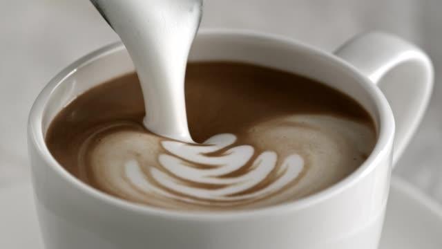 latte cappuccino-tasse in zeitlupe gießen - milchkaffee stock-videos und b-roll-filmmaterial