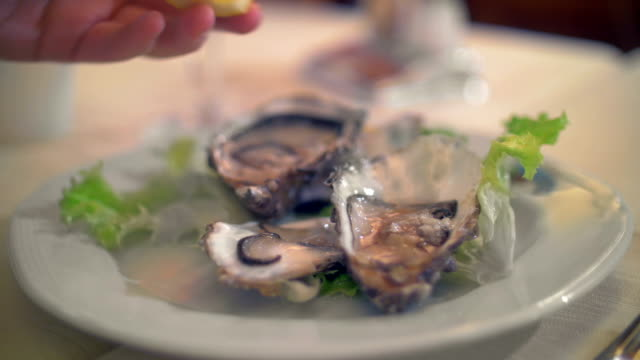 Pouring lemon juice on oysters video