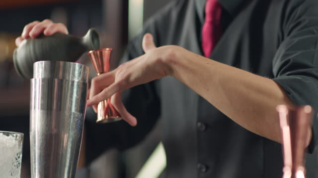Pouring liqueur from jigger into the shaker