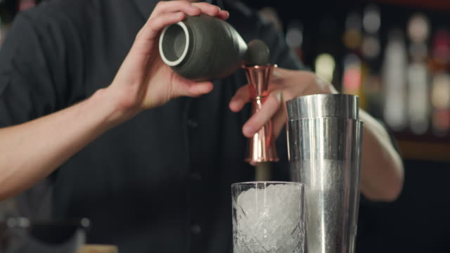 Pouring liqueur into the jigger from jug