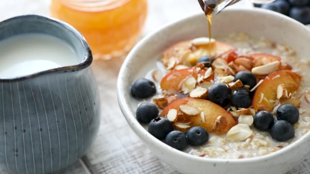 vídeos de stock e filmes b-roll de pouring maple syrup on breakfast porridge with fruits - oats