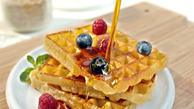 SLO MO LD Pouring maple syrup over waffles