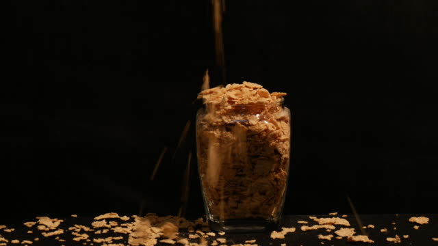 Pouring mass cornflakes into a glass on black video