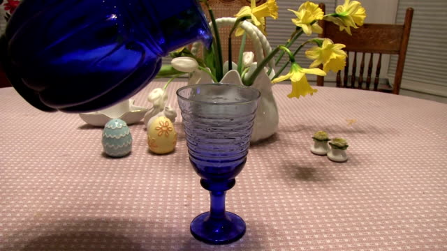 Pouring milk from blue pitcher to glass on decorated table video