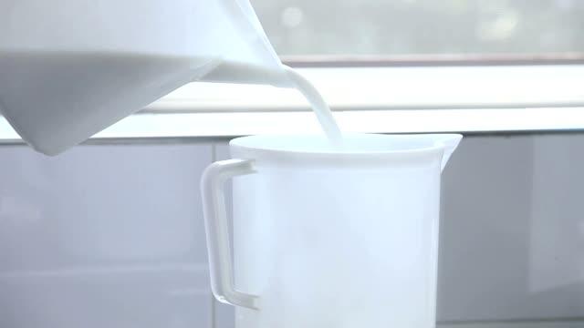 versare il latte dalla brocca - lattaio video stock e b–roll