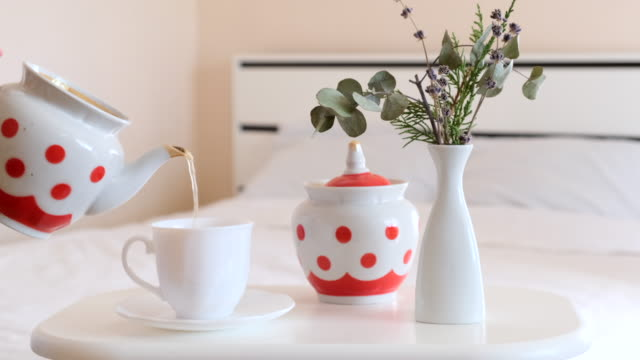 pouring milk in hot coffee. morning breakfast concept. breakfast in bed. adding milk in cup or mug of warm cappuccino - lattaio video stock e b–roll