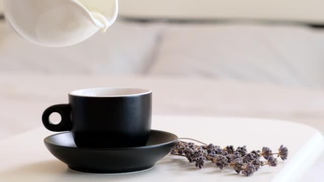 versando latte nel caffè caldo. concetto di colazione mattutina. colazione a letto. aggiunta di latte in tazza o tazza di cappuccino caldo - lattaio video stock e b–roll