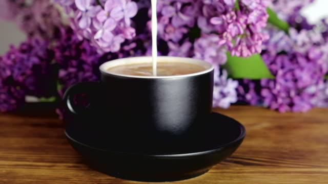pouring milk in hot coffee - lattaio video stock e b–roll