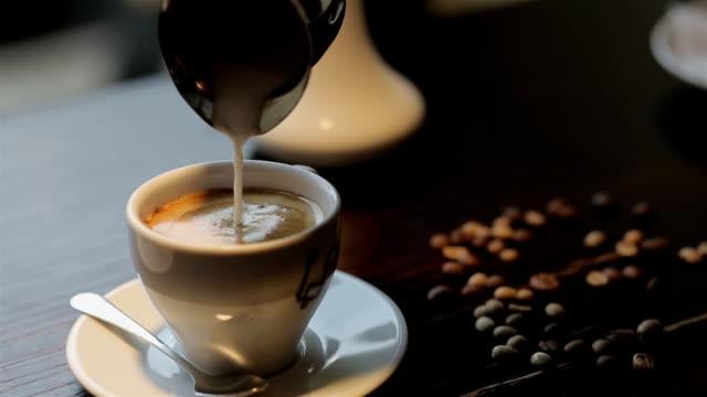 カフェでコーヒーにミルクを入れる ビデオ