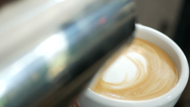 Pouring milk into cup of hot coffee , make latte art video