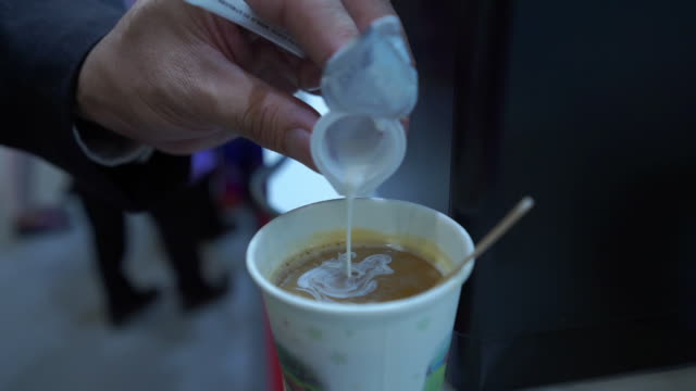 Pouring milk into cup of hot coffee