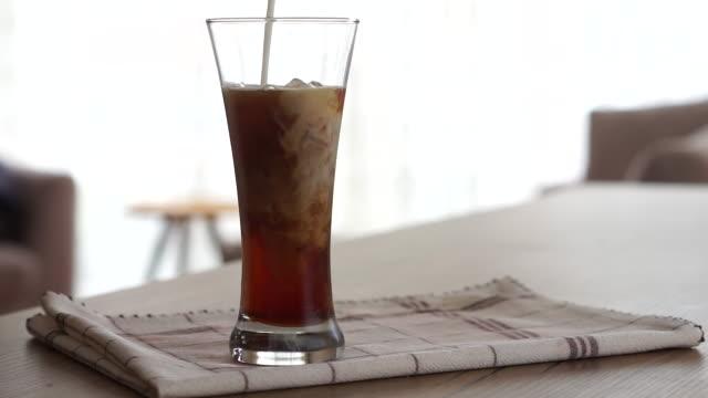 vídeos de stock e filmes b-roll de pouring milk into iced coffee - café gelado