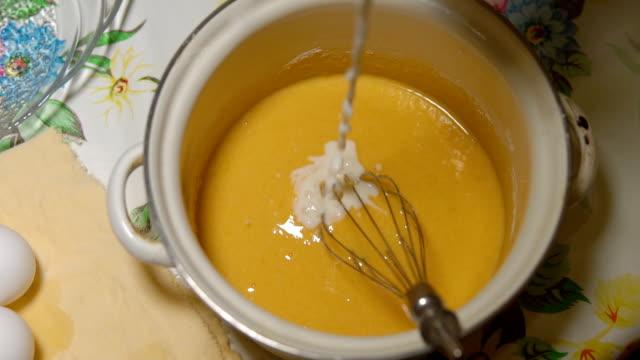 hälla mjölk i äggsmeten i en kastrull - vaniljsås bildbanksvideor och videomaterial från bakom kulisserna