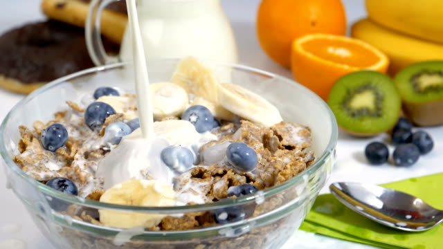 Pouring milk on cereals flakes and fruits for breakfast in slow motion video