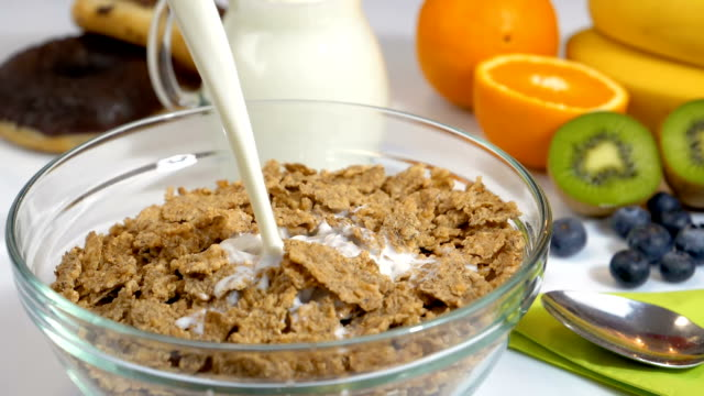 Pouring milk on cereals flakes for breakfast in slow motion video