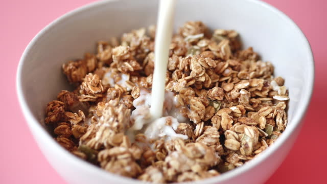 vídeos de stock e filmes b-roll de pouring milk on whole grain cereal cornflakes in white bowl, slow motion. - granola