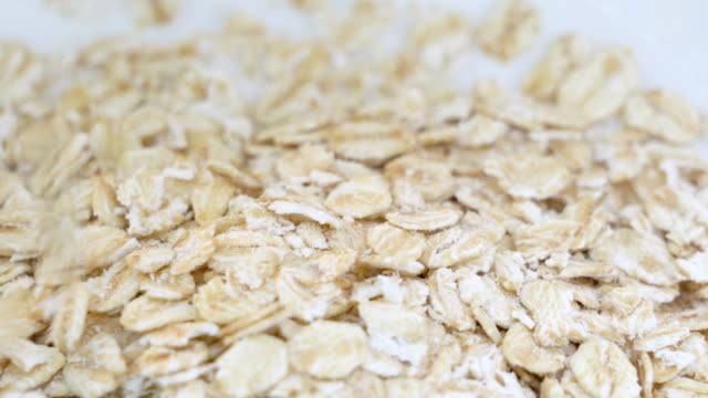 Pouring Oat flakes close up.
