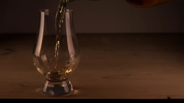 pouring of single malt whisky into tulip glass - scotch whisky video stock e b–roll