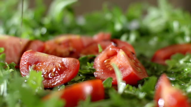 SLO MO Pouring Oil Over Salad HD1080p: SLOW MOTION MEDIUM DOLLY shot of pouring oil over chopped red tomato and arugula. tomato salad stock videos & royalty-free footage