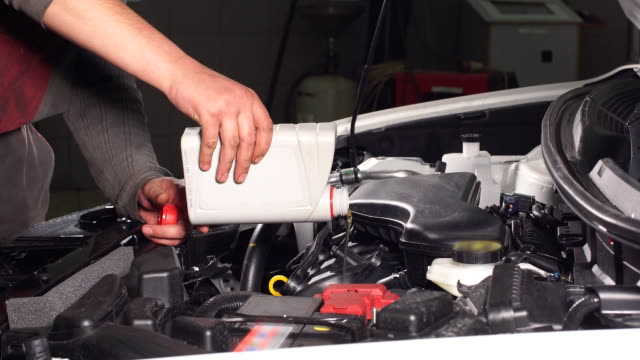 Pouring oil to car engine, close up video