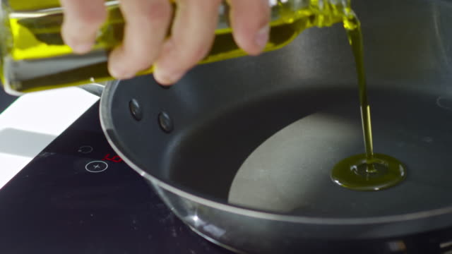 pouring olive oil into pan - olio d'oliva video stock e b–roll